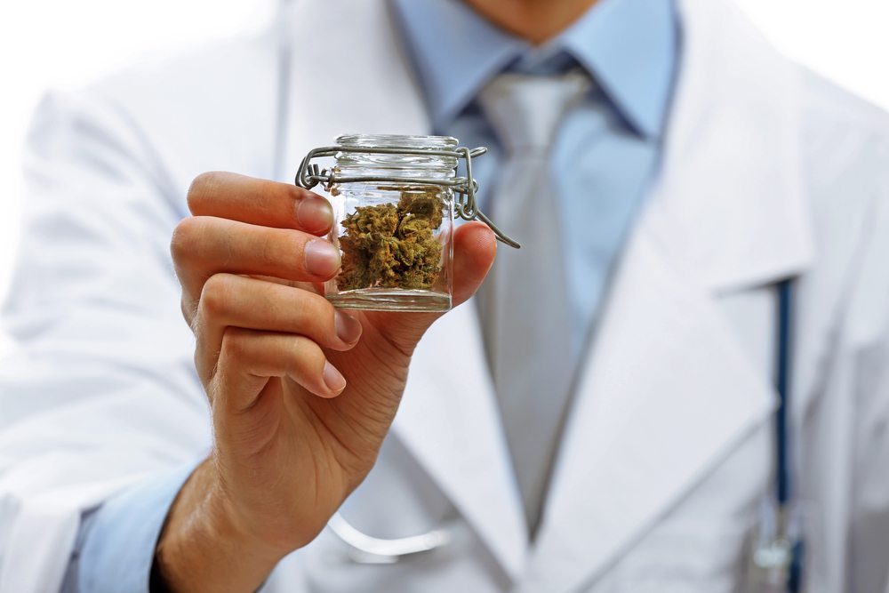 Doctor hand holding bottle with medical cannabis close up